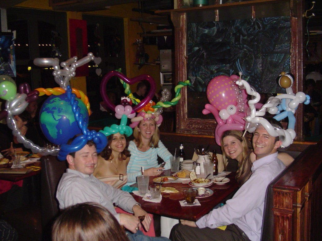 Happy people with balloon hats at a restaurant